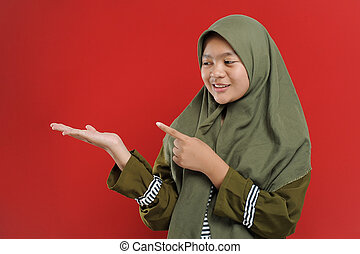 Young Beautiful Muslim woman showing blank copy space, welcome gesture, presenting something