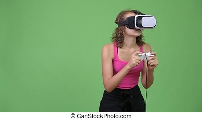 Young beautiful nerd woman playing games and using virtual reality headset