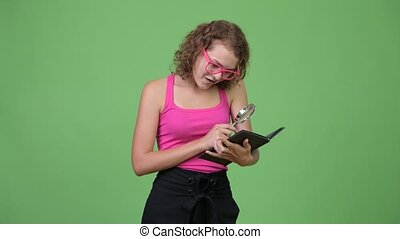 Young beautiful nerd woman reading while using magnifying...