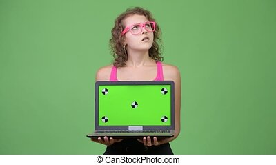 Young beautiful nerd woman thinking while showing laptop -...