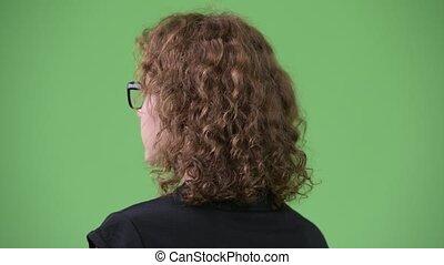 Young beautiful nerd woman wearing eyeglasses while looking back