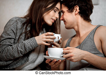 Young beautiful pair of lovers drink tea (coffee) in bed