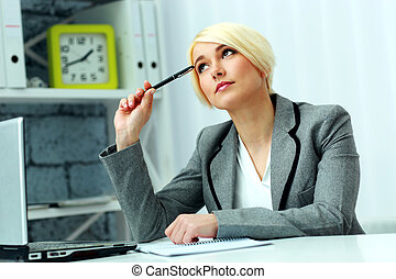 Young beautiful pensive businesswoman sitting at the table and looking up in office