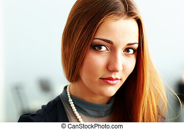Young beautiful pensive woman looking at camera
