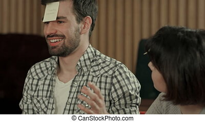 Young beautiful people at cafe table playing name game with sticker notes sticked to their forehead