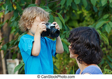 Young beautiful photographer with a camera shoots her mother...