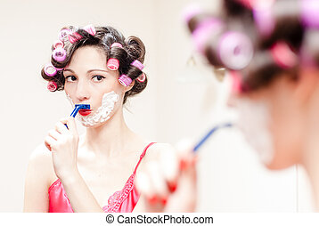 Young beautiful pinup woman shaving mustache with razor and...