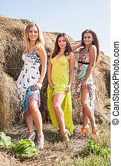 Young beautiful playful women near hay stacks