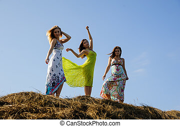 Young beautiful playful women on hay stacks
