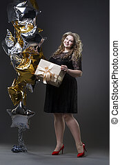 Young beautiful plus size model in black dres with gift box, xxl woman on gray studio background