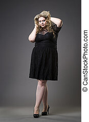 Young beautiful plus size model in black dres, xxl woman on gray studio background