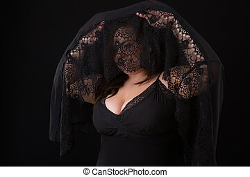 Young beautiful plus size model in black dress and black lace, xxl woman on gray studio black background