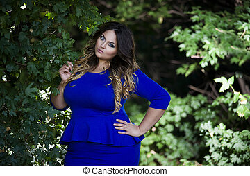 Young beautiful plus size model in blue dress outdoors, xxl...