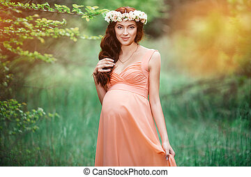 Young beautiful pregnant girl with long brown hair in peach dress with flower wreath on her head