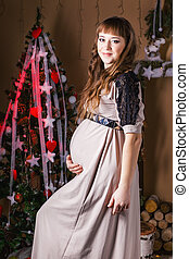 Young beautiful pregnant woman in a long  dress near new year tree