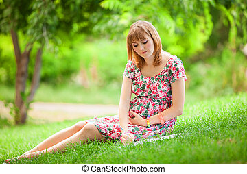Young beautiful pregnant woman in the park