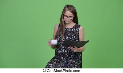 Young beautiful pregnant woman reading book and drinking coffee