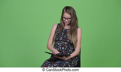 Young beautiful pregnant woman reading book