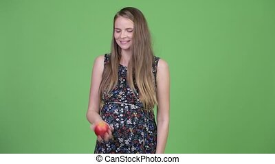 Young beautiful pregnant woman throwing apple in the air