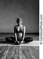 Young beautiful  pregnant yoga posing in studio