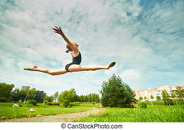 Young beautiful preteen girl doing gymnastics outdoors