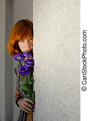 Young beautiful red hair woman holding purple chinese rose copy space