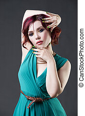 Young beautiful red-haired caucasian woman in aquamarine dress posing in studio on gray background, professional makeup and hairstyle