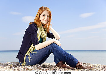 Young beautiful red-haired girl at the beach in spring time.