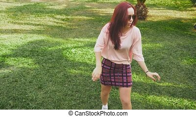 young beautiful red-haired girl dancing in the park. woman...