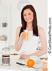 Young beautiful red-haired woman drinking a glass of orange juice