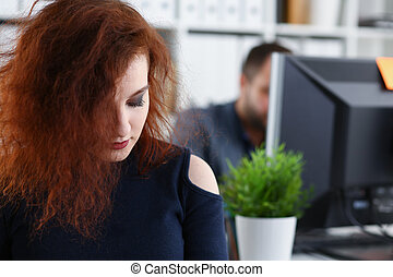 young beautiful red haired woman sit at table in office in cabinet of her boss