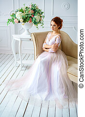 young beautiful red-haired woman sitting in a beautiful delicate dress on the sofa, bride