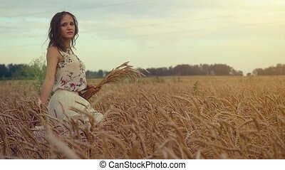 Young beautiful romantic woman walking in a wheat field. Hand of a young girl touching corn ears in a field at sunset in slowmotion.