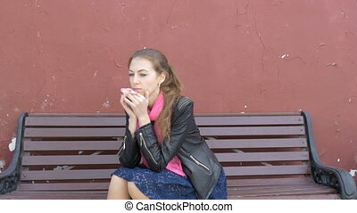 Young beautiful sad girl is sitting on a bench. Sad...
