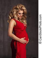 Young beautiful sexy and stylish pregnant woman in red