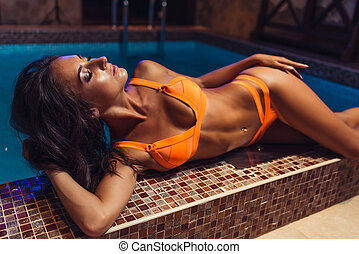 Young beautiful sexy fitness girl in swimsuit posing in the pool.