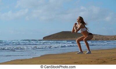 young beautiful sexy woman doing sports on beach, sunrise,...
