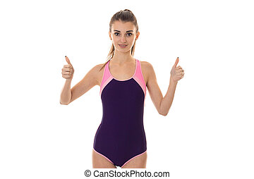 young beautiful slender girl in body swimsuit looks into the camera and shows the class hands