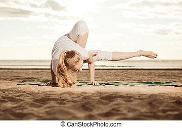 Young beautiful slim woman practices yoga on the beach at...