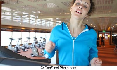 slim woman running in gym - young beautiful slim woman...