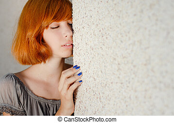 Young beautiful woman in jeans standing near wall negative space