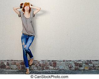 Young beautiful slim woman standing near wall negative space...