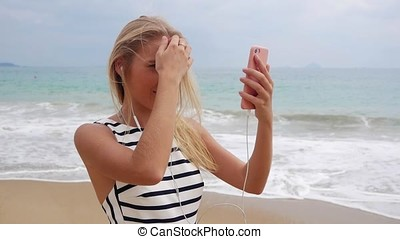 Young beautiful slim woman with long blonde hair in black and white dress looks in her phone, the girl uses a phone instead of a mirror and adjusts her hair. Curvy hair. A woman is walking along the beach on a sunny summer day.