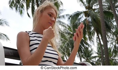 Young beautiful slim woman with long blonde hair in black and white dress looks in her phone, the girl uses a phone instead of a mirror and adjusts her hair. Curvy hair.