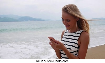 Young beautiful slim woman with long blonde hair in black and white dress standing on the coast and using smartphone over background at storm on the sea.. Girl on the beach touching screen and smile.