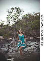 Young beautiful smiles woman in long turquoise dress standing In a sea by the stones. Retro colors