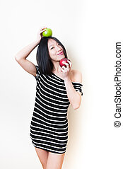 Young beautiful smiling asian woman with green and red apples