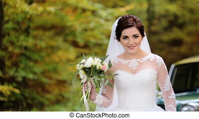Young beautiful smiling bride holding wedding bouquet of flowers  pose on camera.