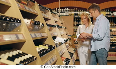 Young Beautiful Smiling Couple Choose Wine In The Supermarket