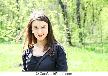 young beautiful smiling girl on a background of green vegetation